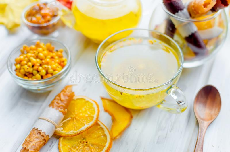 Sea buckthorn tea in glass cup and teapot and fruit pastille. Sea buckthorn tea in glass cup and teapot and many variety fruit pastille and chips on breakfast on stock images