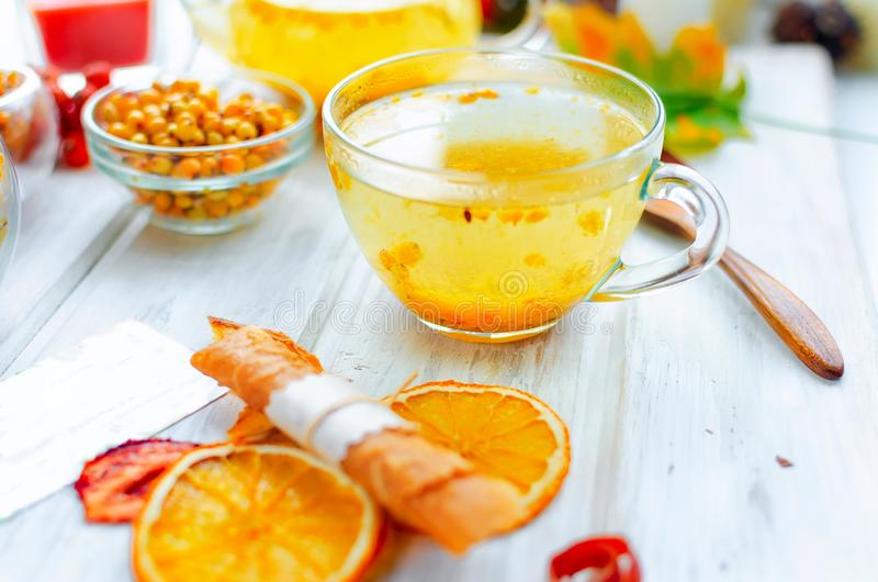 Sea buckthorn tea in glass cup and teapot and many variety fruit pastille and chips on breakfast on white wooden table, natural. Light, selektive focus royalty free stock image