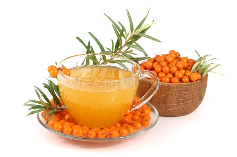 Sea buckthorn tea in a glass and wooden bowl with berries isolated on white background.  stock photo