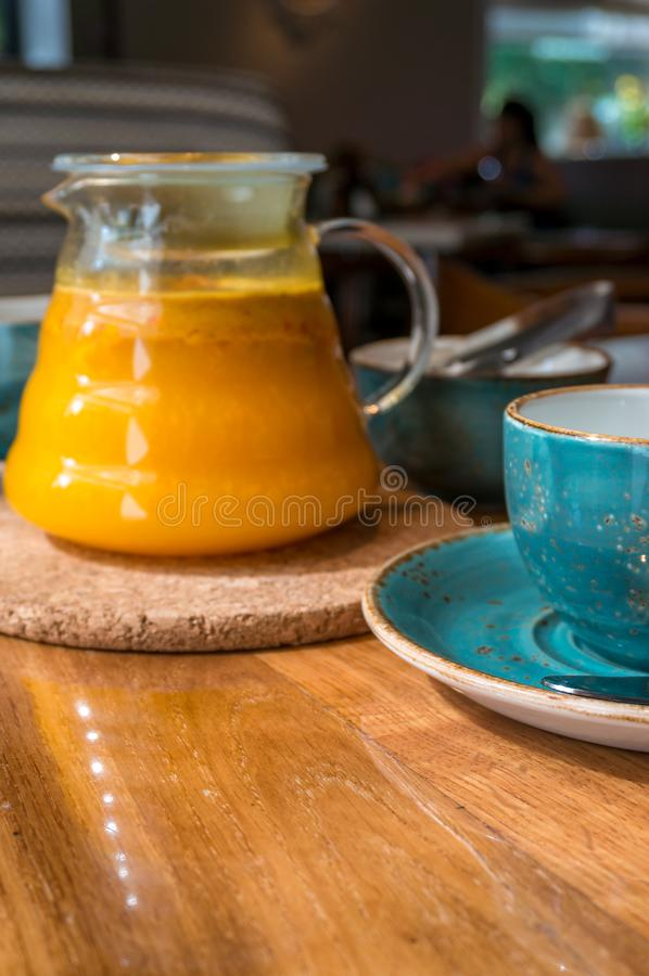 Sea buckthorn tea infusion in glass teapot with teal cup royalty free stock photography