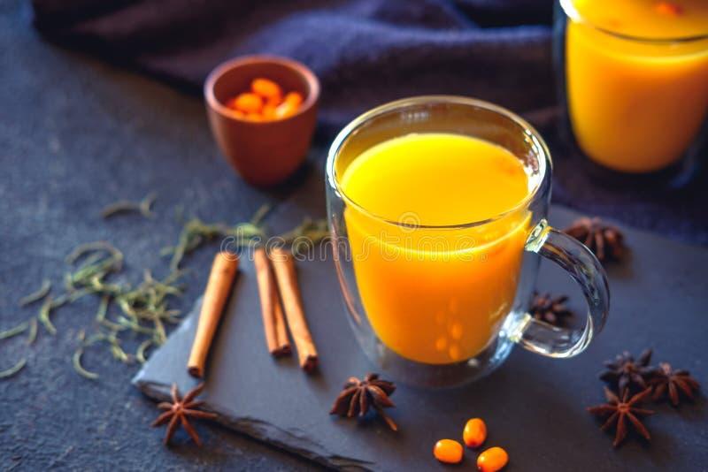 Sea buckthorn tea with orange in a glass cups with fresh sea buckthorn berries. Herbal vitamin tea. royalty free stock image