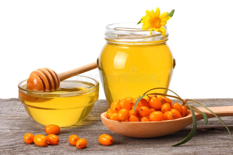 Sea buckthorn in wooden bowl with honey on old wooden table with white background. Fresh ripe berries with leaves royalty free stock photography
