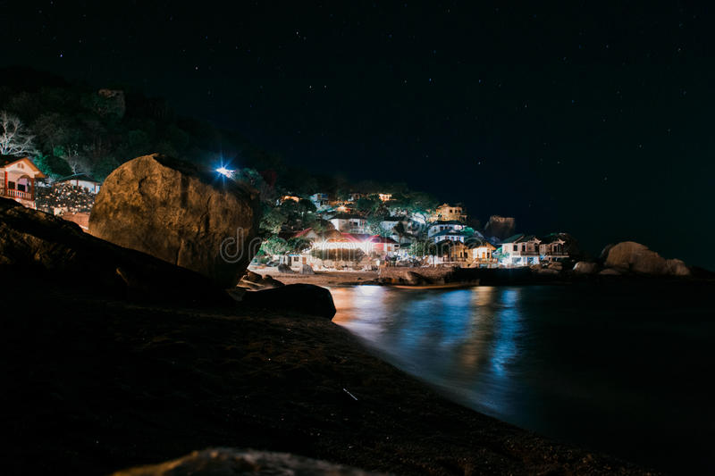 Sea and bungalows during the night stock image