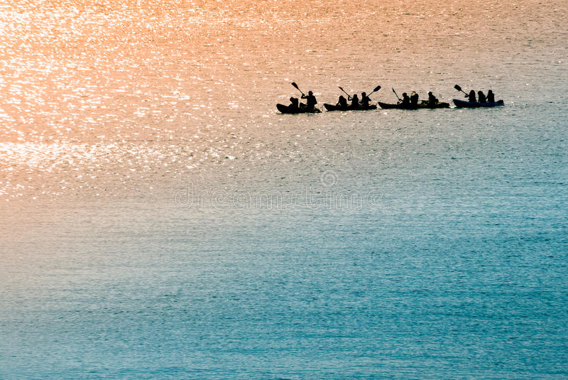 Sea canoeists (water sports) at dawn. A shot of a group of canoeists rowing in the sea early in the morning stock photos