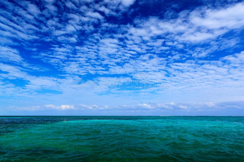 Sea in Caribbean with blue sky and white cloud. Water surface in ocean. Beautiful morning twilight sea landscape. Pink clouds with stock images