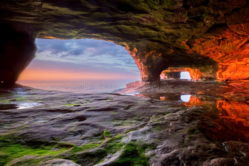 Sea Cave on Lake Superior. The walls of this sea cave radiate a vivid red from the sun setting over Lake Superior. The Pictured Rocks area near Munising Michigan royalty free stock image