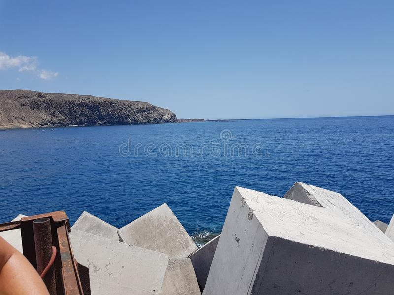 Sea and cliff view at Las Cristianos in Tenerife. Sea view with man made concrete cube blocks at Las Cristianos in Tenerife on a beautiful sunny day with blue stock photo