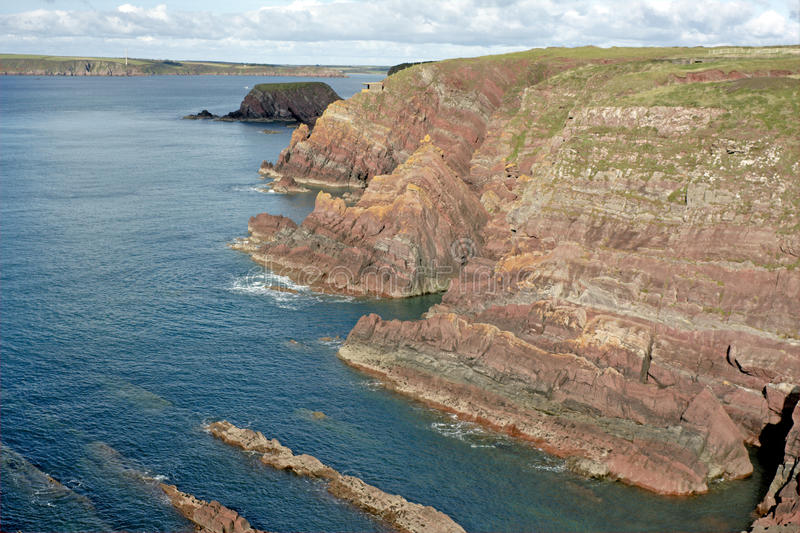 Sea Cliffs in Wales. Scenic view of layered sandstone cliffs and a rocky inlet on the coast of Pembrokeshire. Wales, UK royalty free stock photography