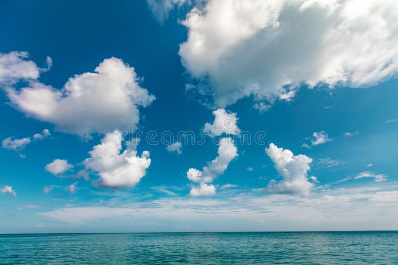 Sea with clouds. Summer season beautiful blue calm sea and deep blue sky with fluffy clouds stock photo