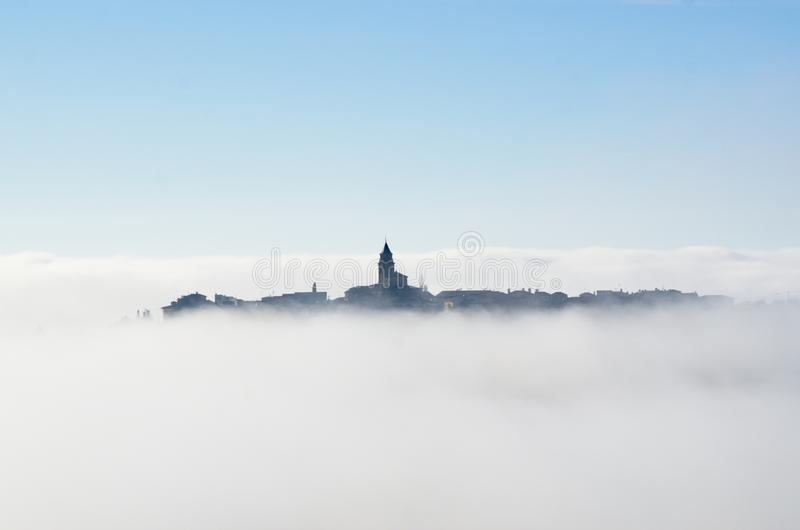 Sea of clouds. Village covered in fog with some houses and the church tower protruding above the clouds. Winter landscape. Thermal inversion. Sea of clouds royalty free stock photos