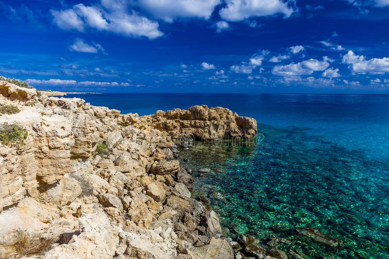 Sea coast with clear turquoise water, stone cape, blue sky with clouds stock images