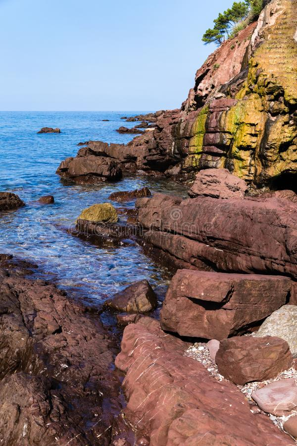 Yellow rock over which the spring waters. Sea coast with large brown stones in the water and yellow rock over which the spring waters royalty free stock photo