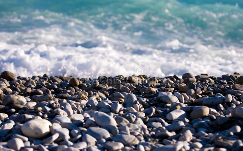 Sea coast with pebbles. Focus on pebbles royalty free stock photos