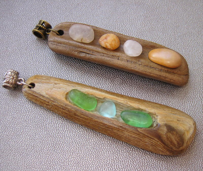 Sea driftwood pendants. Pendants made from driftwood , sea glass and natural stones stock image