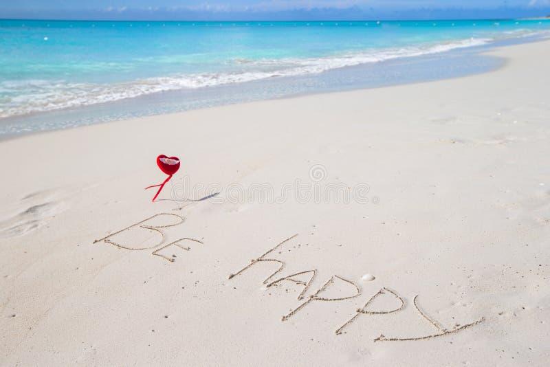 Sea feliz escrito en una playa tropical arenosa fotografía de archivo