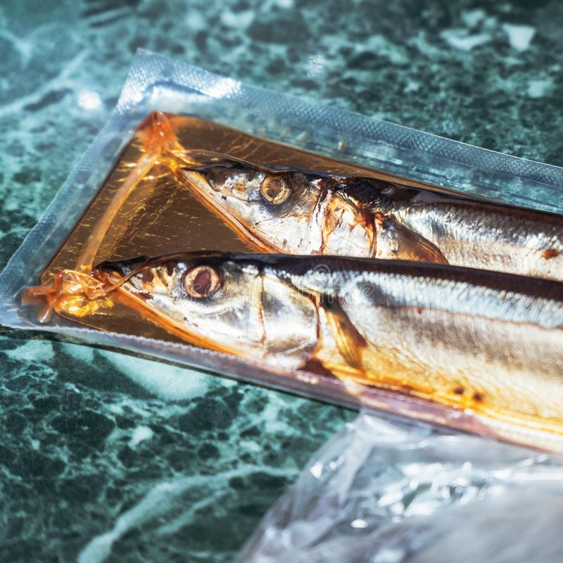 Sea fish saury in vacuum packaging. On the table. Selective focus stock photo