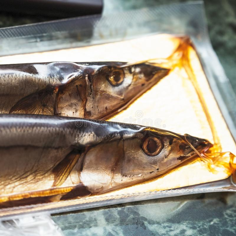 Sea fish saury in vacuum packaging. On the table. Selective focus royalty free stock images