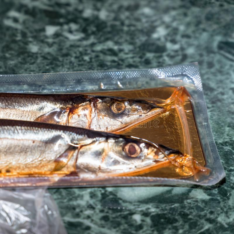 Sea fish saury in vacuum packaging. On the table. Selective focus royalty free stock image