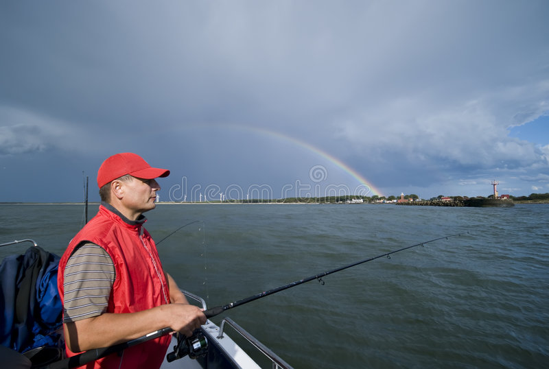 Sea fishing and lucky rainbow stock photos