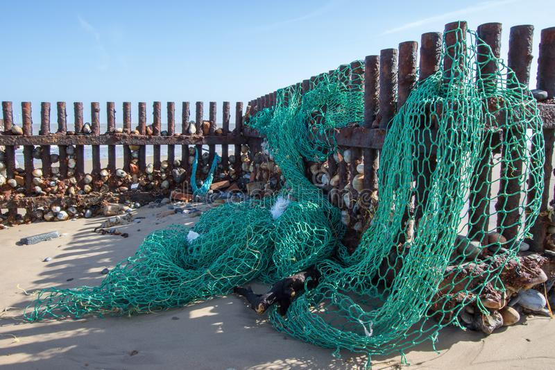 Sea fishing net washed up on the beach. Ocean pollution. Green nylon plastic environmental hazard and a threat to wildlife royalty free stock images