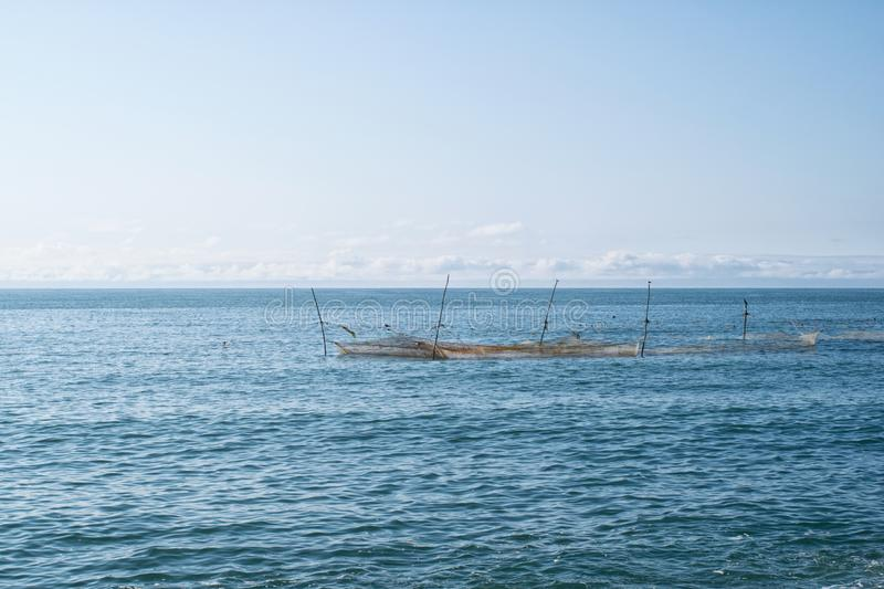 The sea with fishing nets on poles on the background of clear sky and a small group of clouds in the distance. The sea with fishing nets on poles against the stock photography