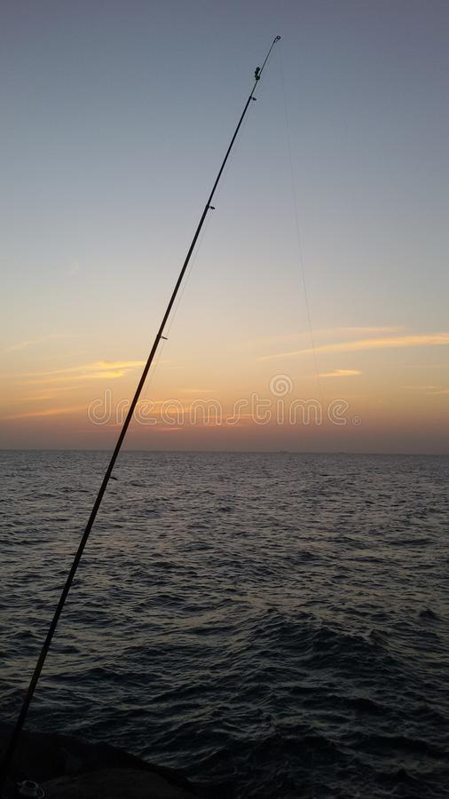 Sea fishing at sunset stock image