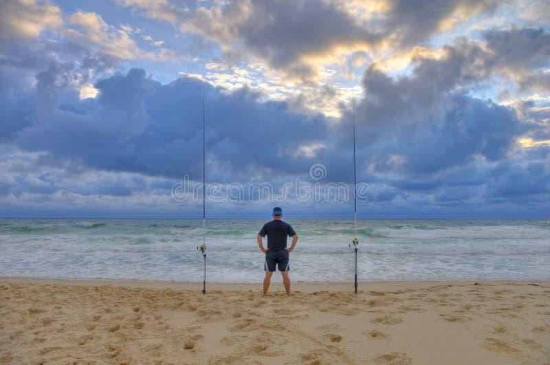 Sea Fishing, surf fishing scene, man waiting for fish royalty free stock photo