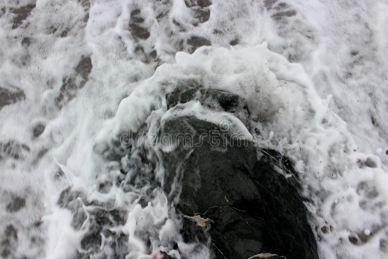 Sea foam around the stone stock photo