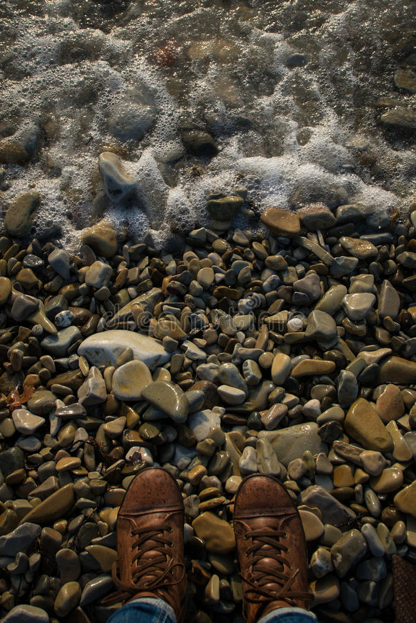 Sea foam on the seashore of pebbles. Legs in sneakers stand on the beach in front of the sea. royalty free stock photos