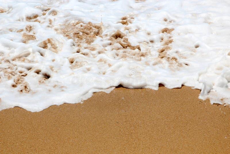 Sea foam on a sparkling beach in Penghu Taiwan. The sea foam is bubbling as it hits the warm brown sand of a beach in Penghu Taiwan royalty free stock photos