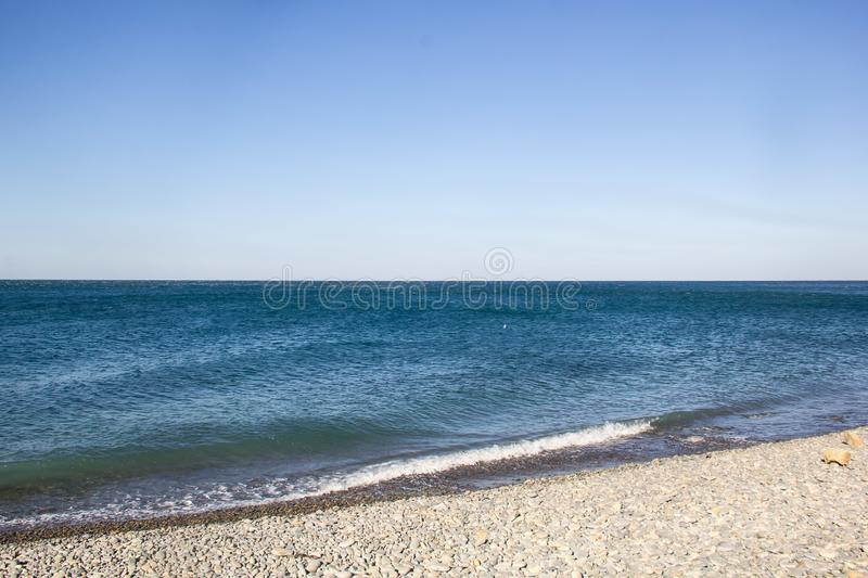 The sea foamy waves on an empty pebble beach royalty free stock images