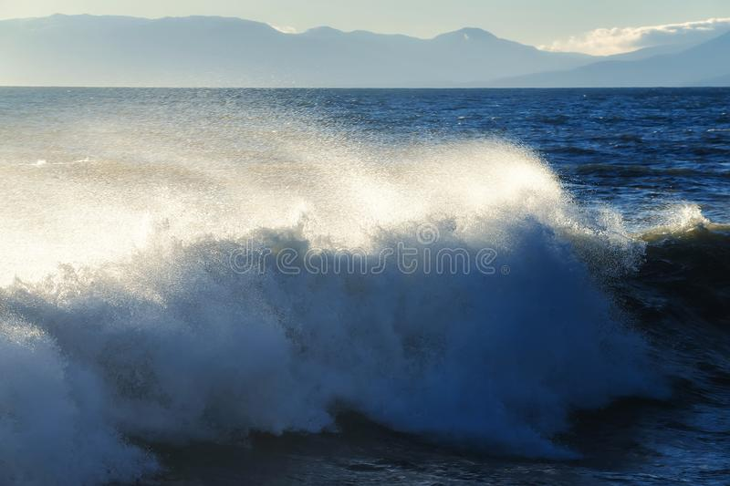 The sea with foamy waves storms against the backdrop of the gloomy sky. And mountain coastline stock image