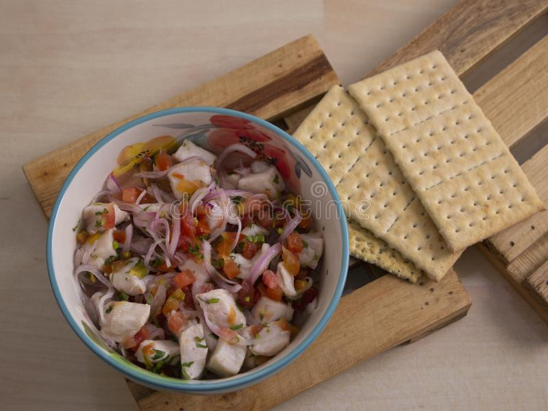 Sea Food Bowl of Ceviche with Onions Tomato and Parsley with Lime and Salt Crackers royalty free stock images