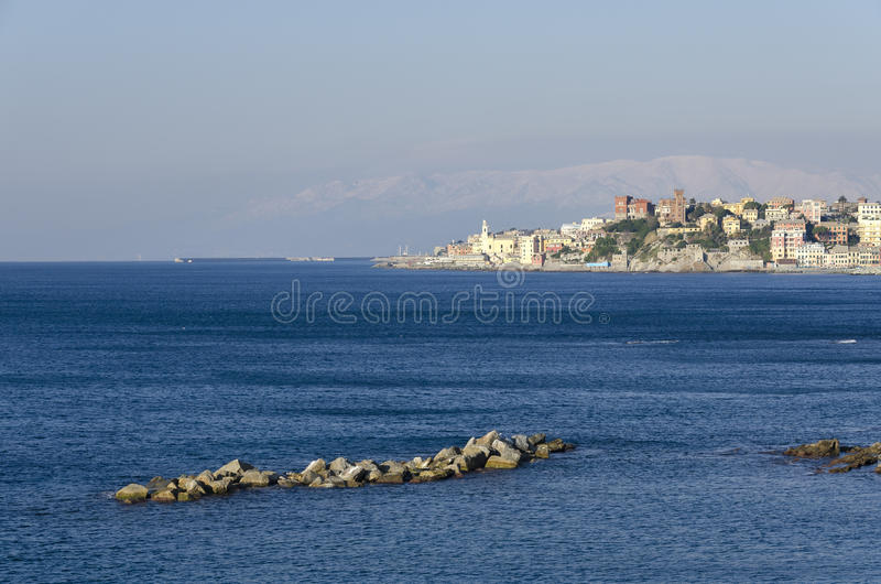 Sea in Genoa. Boccadasse with snowy mountains in Genoa royalty free stock photo