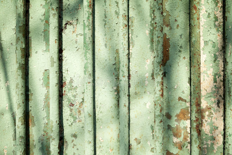 Sea green color old cracked wall background. Painted metal fence with bars grunge texture stock photography
