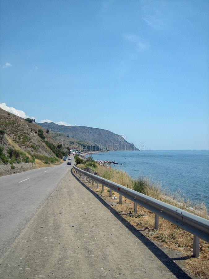 Between the sea and the hills road to the seaside resort on a hot Sunny day stock photography