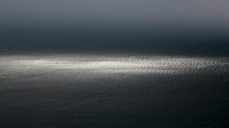 Sea horizon fuses with sky. Photo of spectacular dark marine seashore sea horizon with ripples fuses with grey sky at dusk bleakness over seascape background royalty free stock photos