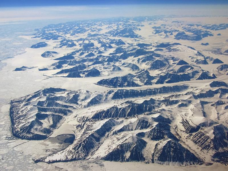 Spring Thaw over Eastern Fjords of Greenland. The sea ice is melting along the eastern fjords of Greenland in June, clearly marking the edge between the barren royalty free stock images