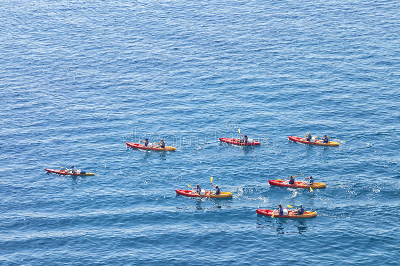 Sea kayaking in red canoes stock images