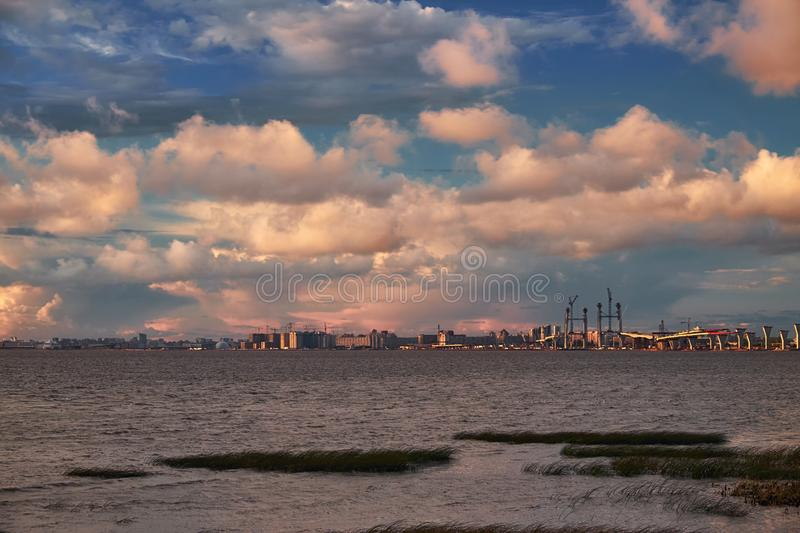 Sea landscape with bridge road construction and cranes on horizon in sunset light. Landscape with gulf water clouds Saint Petersburg royalty free stock photography