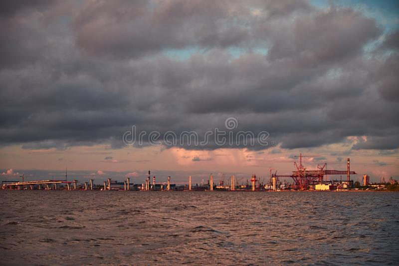 Sea landscape with bridge road construction and cranes on horizon in sunset light. Landscape with gulf water clouds Saint Petersburg industrial zone royalty free stock photography