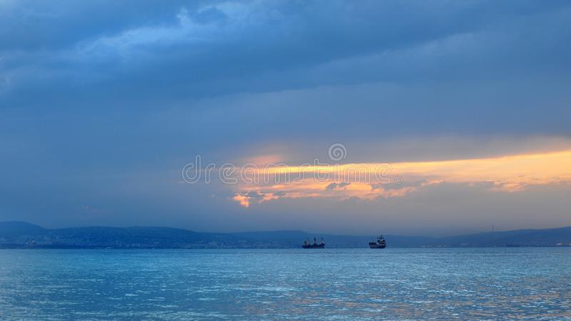 Seascape with wonderful views of ships, mountains, sea and the setting sun stock photos