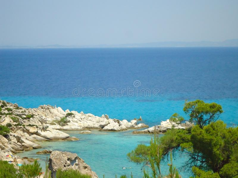 Sea landscape in Greece with blue sea and green trees royalty free stock photos