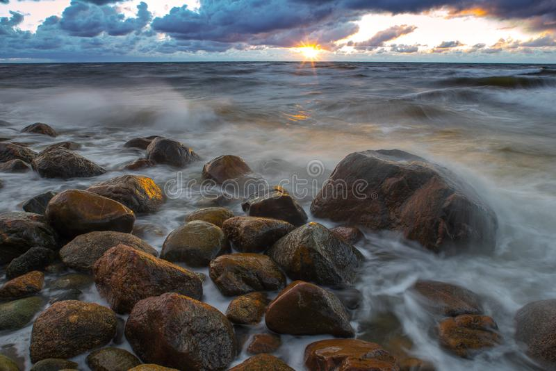 A sea landscape with rocks, a storm and a setting sun. Waves, rocks, storm and clouds.n royalty free stock photo