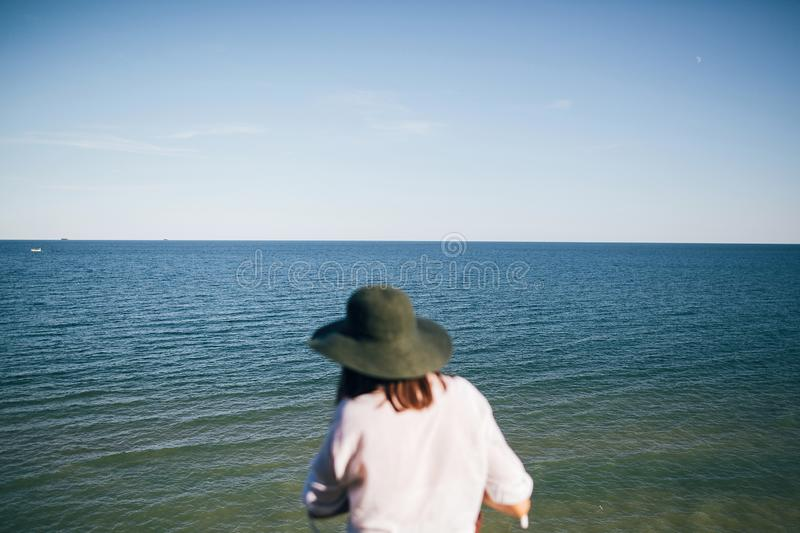 Sea landscape in sunny evening light, view from sandy cliff and blurred boho girl in hat back. Happy young hipster woman relaxing. On tropical island beach royalty free stock photography