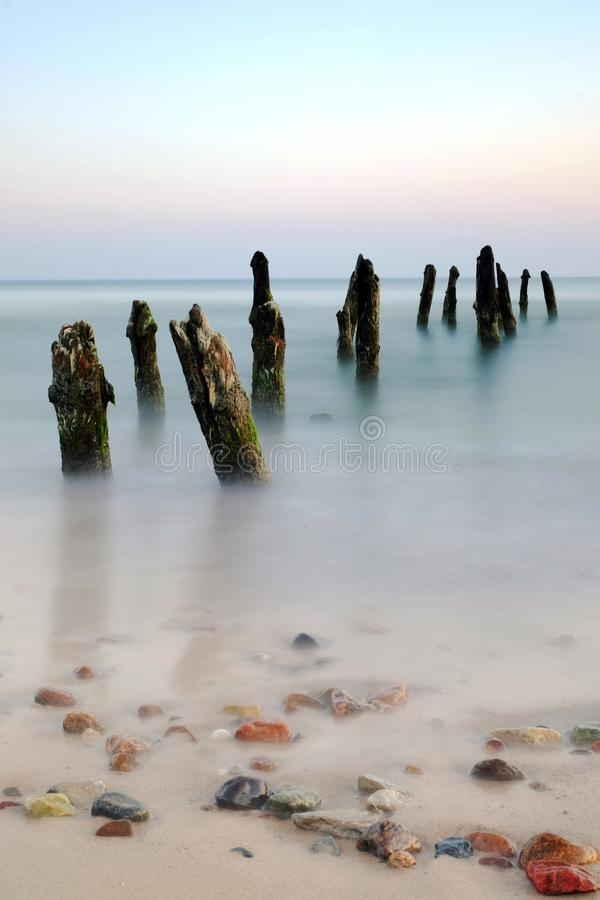 Sea landscape during sunrise, Baltic coast, Kolobrzeg, Poland. Breakwaters on the coast of the Baltic Sea in the rays of the rising sun stock photo