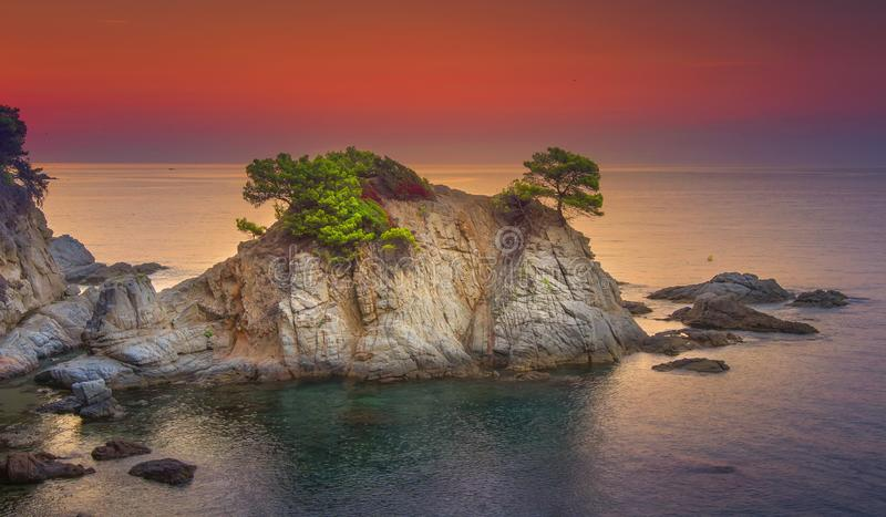 Sea landscape at sunrise. Beautiful view of cliff in Mediterranean at dawn in morning. Bright red sky over Spanish coast royalty free stock photography