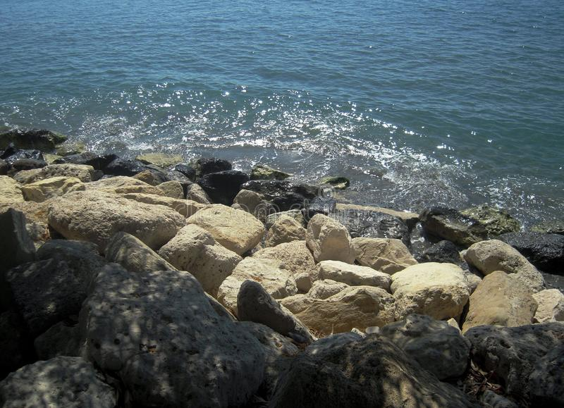 Sea landscape, white and black sea rocks and glitter wave. Sea landscape, white and black sea rocks and glitter wave, daytime, sunshine, nature background royalty free stock photos