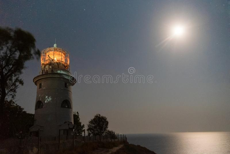 Sea lighthouse on the shore at night stock photos