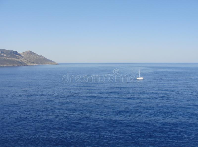 Sea with lonely white sail boat stock photography